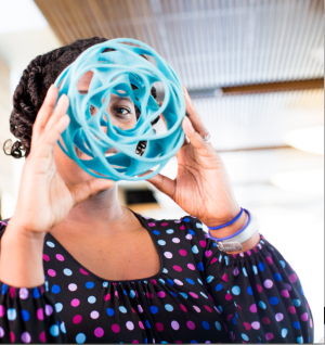 Woman looking through blue spiral ball